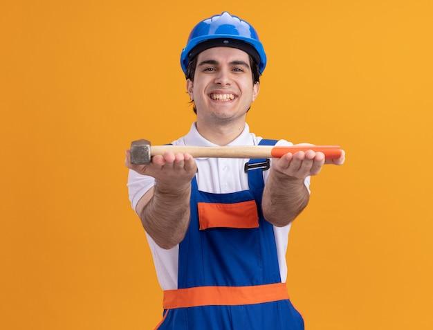 Homem jovem construtor feliz com uniforme de construção e capacete de segurança, demonstrando o martelo olhando para a frente, sorrindo alegremente em pé sobre a parede laranja