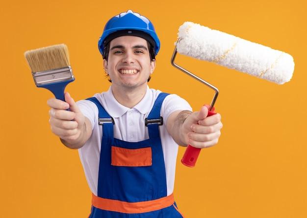 Homem jovem construtor feliz com uniforme de construção e capacete de segurança segurando pincel e rolo olhando para frente sorrindo alegremente em pé sobre a parede laranja