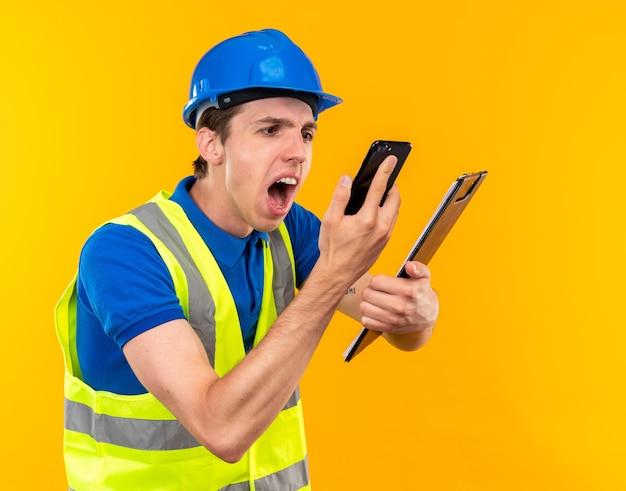 Homem jovem construtor furioso, de uniforme, segurando a prancheta e olhando para o telefone na mão