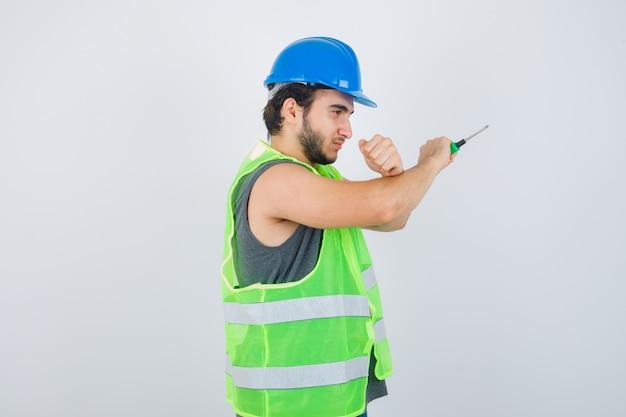 Homem jovem construtor mostrando gesto de protesto, segurando a chave de fenda de uniforme e olhando sério, vista frontal.