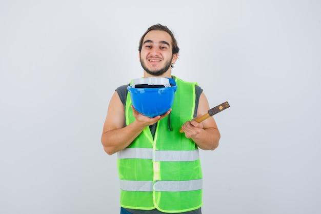 Homem jovem construtor mostrando o martelo e o capacete em uniforme de trabalho e olhando alegre, vista frontal.