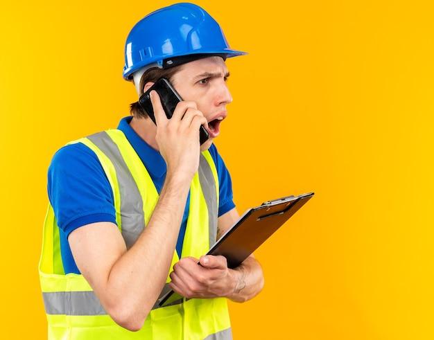 Homem jovem construtor preocupado com uniforme segurando uma prancheta e falando ao telefone