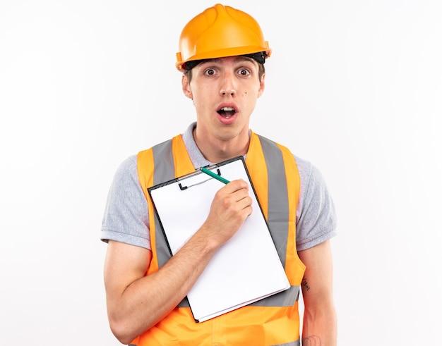 Homem jovem construtor preocupado, de uniforme, segurando uma prancheta com um lápis