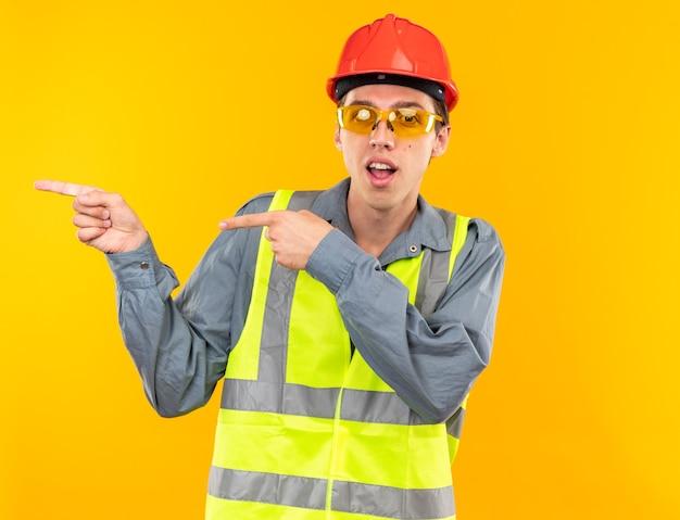 Homem jovem construtor satisfeito, de uniforme, com óculos apontando para o lado isolado na parede amarela com espaço de cópia
