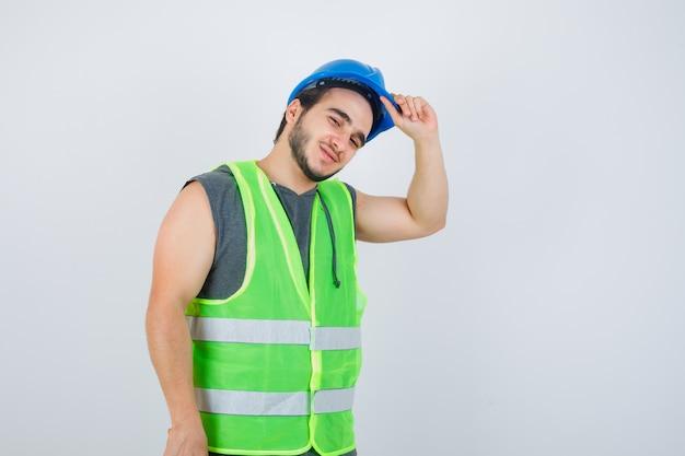 Homem jovem construtor segurando a mão no capacete em uniforme de trabalho e parecendo alegre. vista frontal.