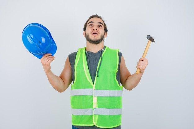 Homem jovem construtor segurando o martelo e o capacete enquanto levanta as mãos em uniforme de trabalho e olhando perplexo, vista frontal.