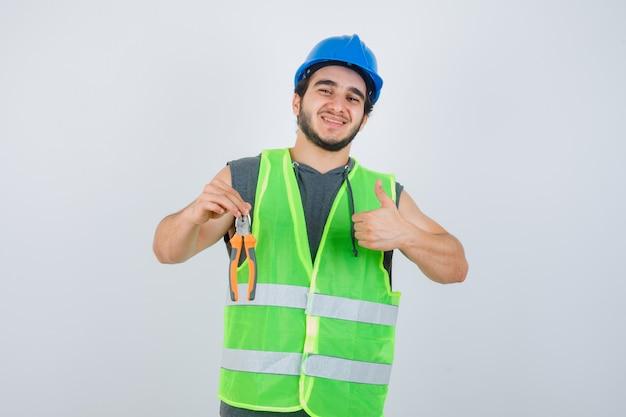 Homem jovem construtor segurando um alicate enquanto aparecendo o polegar em uniforme de trabalho e olhando alegre. vista frontal.