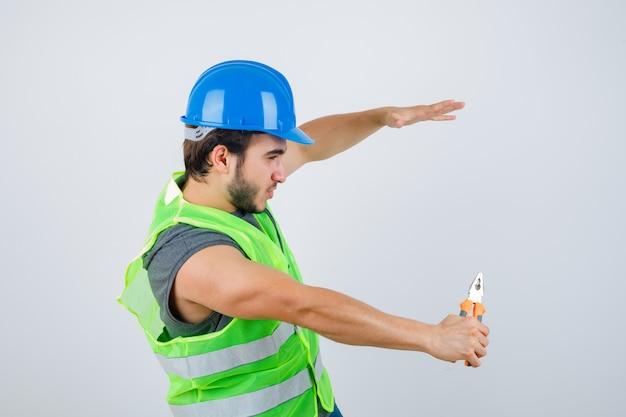 Homem jovem construtor segurando um alicate enquanto finge pegar algo em uniforme de trabalho e parece autoconfiante. vista frontal.