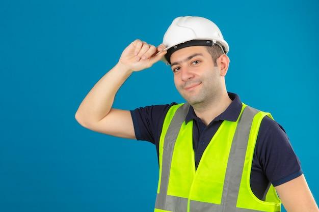 Homem jovem construtor usando capacete branco e um colete amarelo, com um sorriso no rosto tocando seu capacete de segurança branco construção azul isolado
