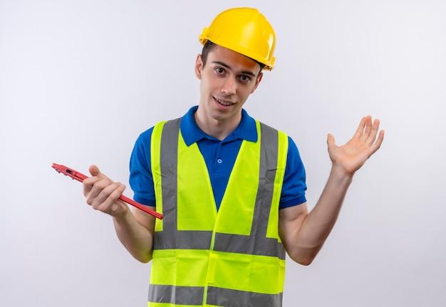 Homem jovem construtor usando uniforme de construção e capacete de segurança segurando um alicate de ranhura