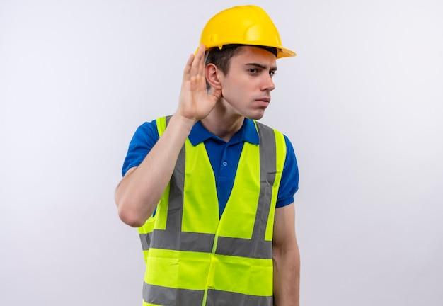 Homem jovem construtor usando uniforme de construção e capacete de segurança tenta ouvir