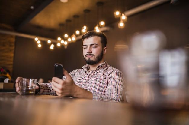 Homem jovem, copo segurando, de, bebida, usando, telefone móvel