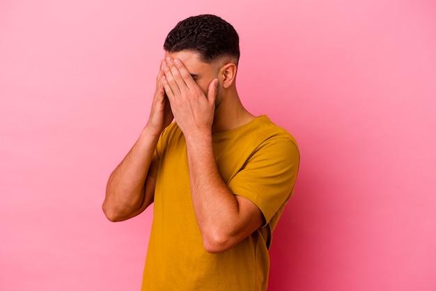 Homem jovem da raça mista isolado no fundo rosa com medo de cobrir os olhos com as mãos.