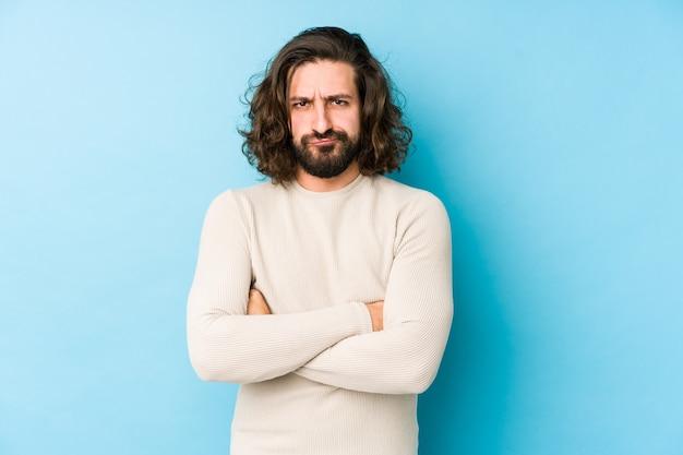 Homem jovem de cabelo comprido isolado em uma parede azul, rosto carrancudo em desgosto, mantém os braços cruzados.
