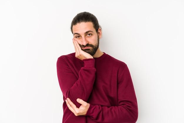 Homem jovem de cabelo comprido isolado em uma parede branca que está entediado, cansado e precisa de um dia relaxante.