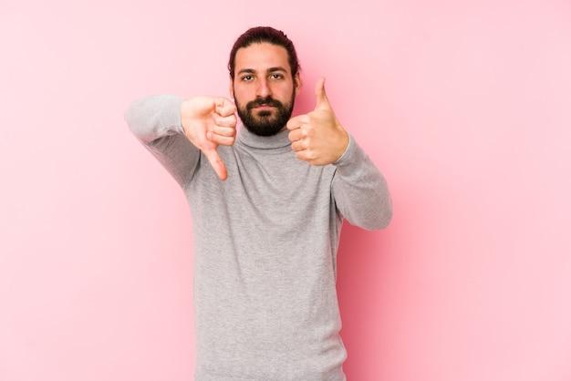 Homem jovem de cabelo comprido isolado em uma parede rosa mostrando os polegares para cima e para baixo, difícil escolher o conceito