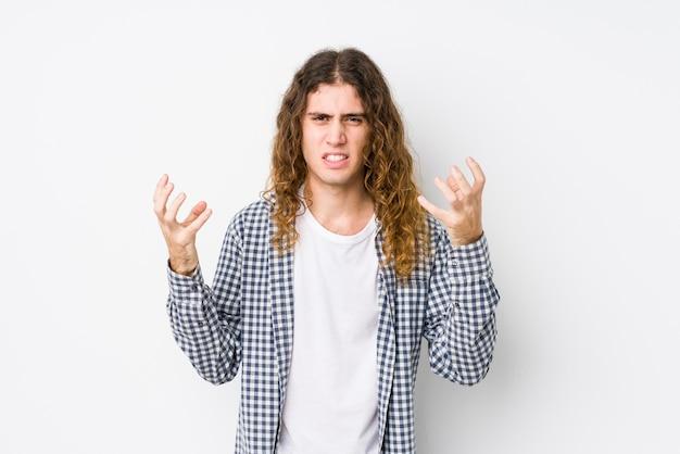 Homem jovem de cabelo comprido posando chateado isolado gritando com as mãos tensas.