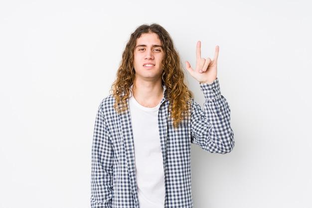 Homem jovem de cabelo comprido posando isolado, mostrando um gesto de chifres como um conceito de revolução.