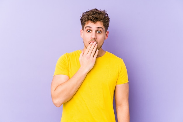 Homem jovem de cabelos cacheados loiros isolado bocejando mostrando um gesto cansado, cobrindo a boca com a mão
