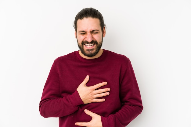 Homem jovem de cabelos longos, isolado em um fundo branco ri alegremente e se diverte mantendo as mãos no estômago.