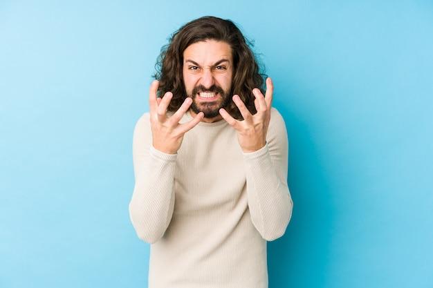 Homem jovem de cabelos longos, isolado em uma parede azul chateado gritando com as mãos tensas.