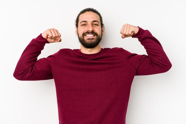 Homem jovem de cabelos longos, isolado em uma parede branca, mostrando o gesto de força com os braços, símbolo do poder feminino