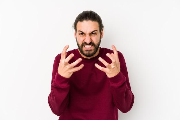 Homem jovem de cabelos longos, isolado em uma virada branca, gritando com as mãos tensas.