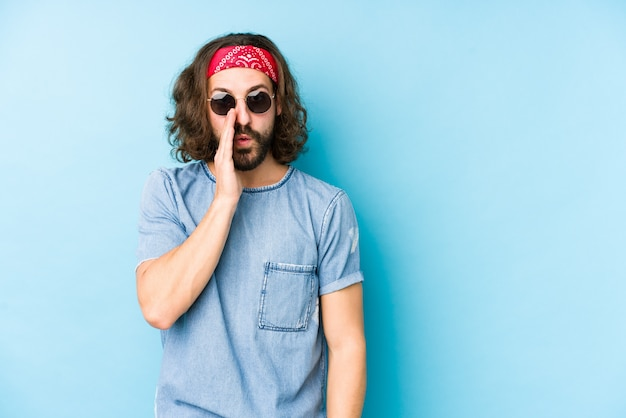 Homem jovem de cabelos longos, vestindo um look festival hipster isolado está dizendo uma notícia secreta de travagem quente e olhando de lado