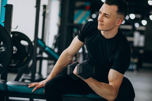 Homem jovem de esportes treinando na academia