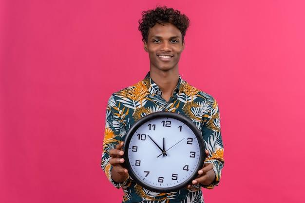 Homem jovem de pele escura com cabelo encaracolado, satisfeito e sorridente, segurando uma camisa com estampa de folhas segurando um relógio de parede com os ponteiros que mostram as horas em um fundo rosa