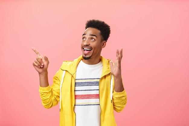 Homem jovem de pele escura empolgado e emocionado com barba e penteado afro, levantando a palma da mão em pose de espanto apontando e olhando para o canto superior esquerdo surpreso e encantado com a parede rosa