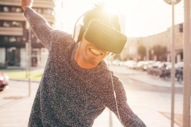 Homem jovem de raça mista ao ar livre usando o visualizador em 3d