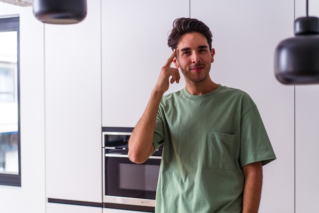 Homem jovem de raça mista em sua cozinha, apontando o templo com o dedo, pensando, focado em uma tarefa.