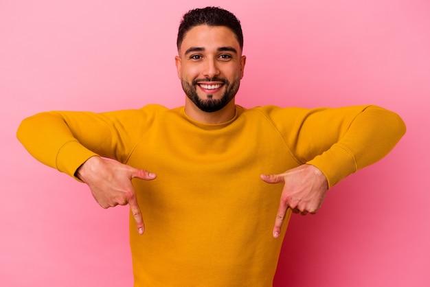 Homem jovem de raça mista isolado em fundo rosa aponta para baixo com os dedos, sentimento positivo.