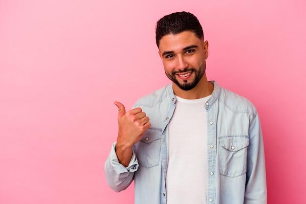 Homem jovem de raça mista isolado em fundo rosa chocado apontando com o dedo indicador para um espaço de cópia.