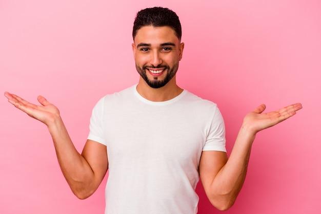 Homem jovem de raça mista isolado em fundo rosa faz escala com os braços, sente-se feliz e confiante.