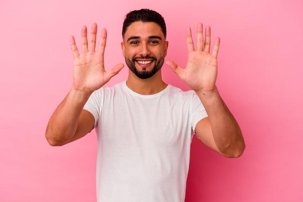 Homem jovem de raça mista isolado em fundo rosa, mostrando o número dez com as mãos.