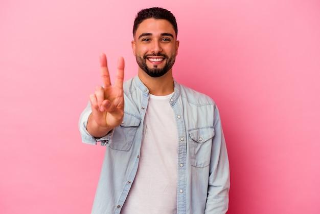 Homem jovem de raça mista isolado em fundo rosa, mostrando sinal de vitória e sorrindo amplamente.