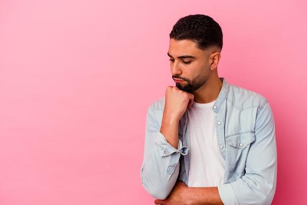 Homem jovem de raça mista isolado em fundo rosa, olhando de soslaio com expressão duvidosa e cética.
