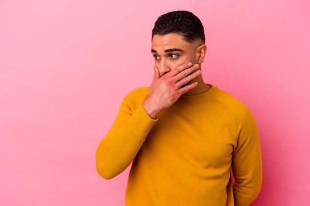 Homem jovem de raça mista isolado em fundo rosa pensativo olhando para um espaço de cópia cobrindo a boca com a mão.