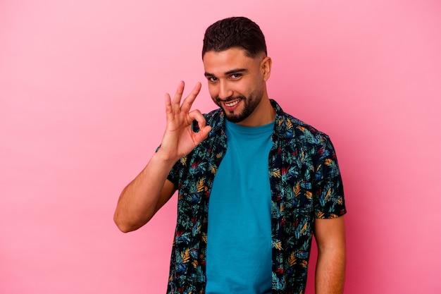 Homem jovem de raça mista isolado em fundo rosa pisca os olhos e segura um gesto de ok com a mão.