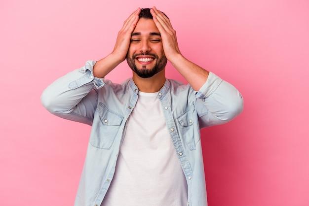 Homem jovem de raça mista isolado em fundo rosa ri com alegria, mantendo as mãos na cabeça. conceito de felicidade.