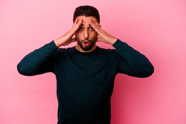 Homem jovem de raça mista isolado em fundo rosa, se divertindo, cobrindo metade do rosto com a palma da mão.