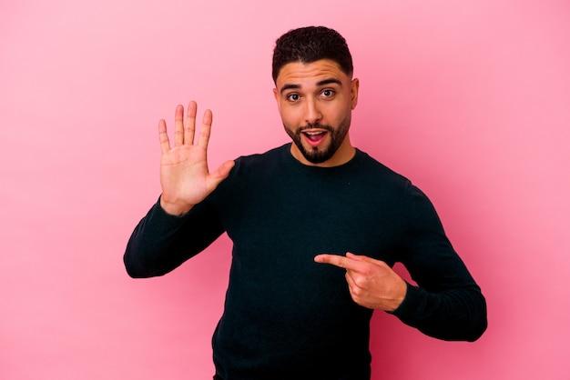 Homem jovem de raça mista isolado em fundo rosa, sorrindo alegre mostrando o número cinco com os dedos.