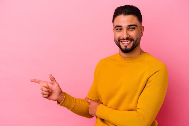 Homem jovem de raça mista isolado em fundo rosa, sorrindo alegremente, apontando com o dedo indicador para longe.