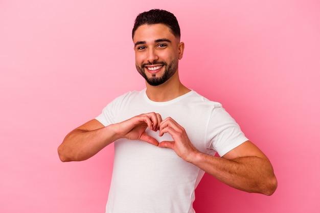 Homem jovem de raça mista isolado em fundo rosa, sorrindo e mostrando uma forma de coração com as mãos.