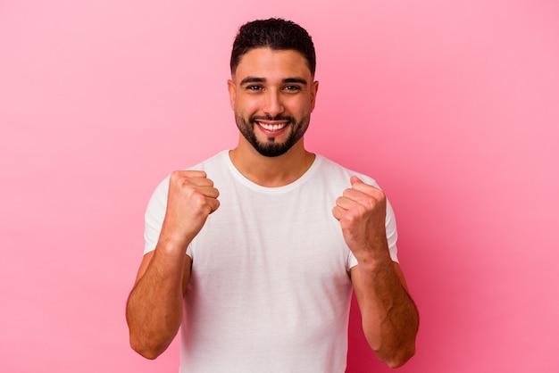 Homem jovem de raça mista isolado em fundo rosa torcendo despreocupado e animado. conceito de vitória.