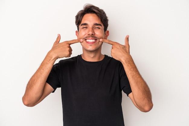 Homem jovem de raça mista isolado em sorrisos de fundo branco, apontando o dedo para a boca.
