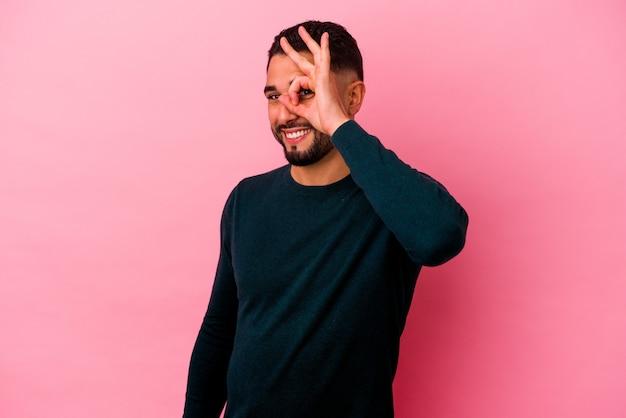 Homem jovem de raça mista isolado em um fundo rosa animado, mantendo o gesto ok no olho.