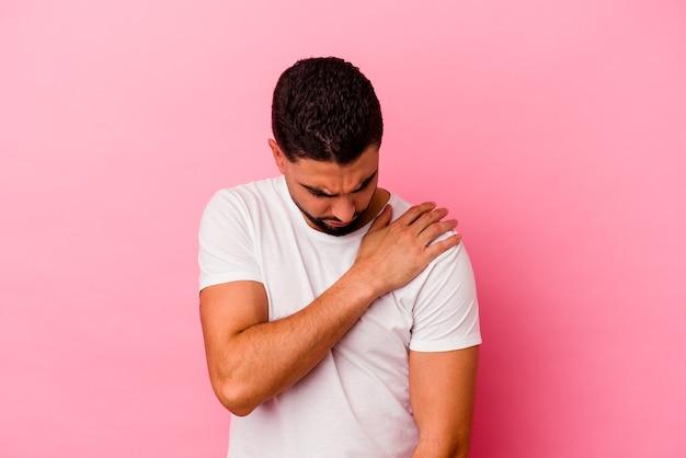 Homem jovem de raça mista, isolado em um fundo rosa, com dor no ombro.